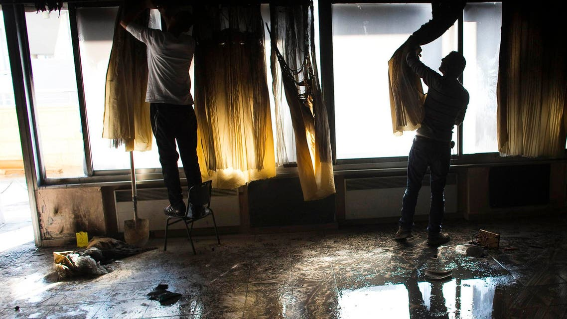 Workers remove the curtains in a torched classroom in an Arab-Jewish school in Jerusalem November 30, 2014. (Reuters)