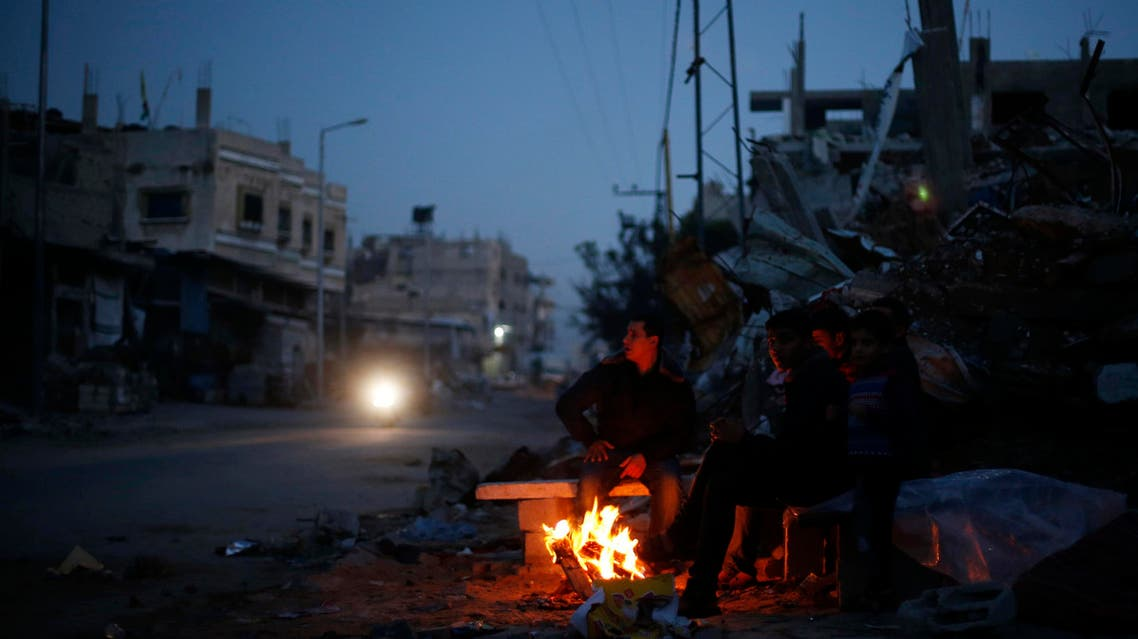 Palestinians warm themselves by a fire near the ruins of houses which witnesses said were destroyed by Israeli shelling during the most recent conflict between Israel and Hamas, in the east of Gaza City. (File photo: Reuters)