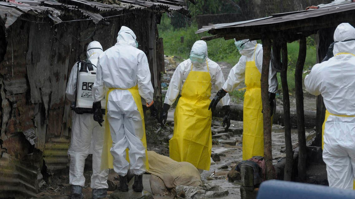 Health workers wearing protective clothing prepare to carry an abandoned dead body presenting with Ebola symptoms at Duwala market in Monrovia, in this August 17, 2014 file photo. (Reuters)