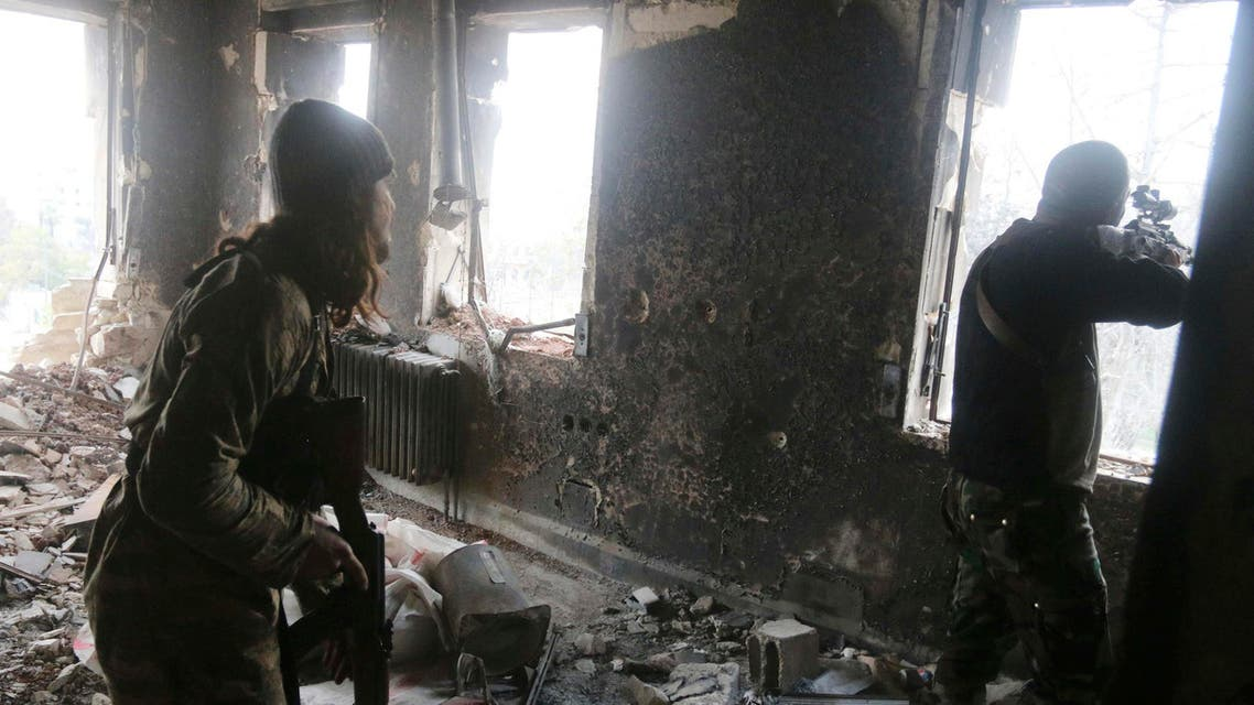 Rebel fighters take positions inside a damaged building during clashes with forces loyal to Syria's President Bashar al-Assad who are stationed in Aleppo's historic citadel December 7, 2014. (Reuters)