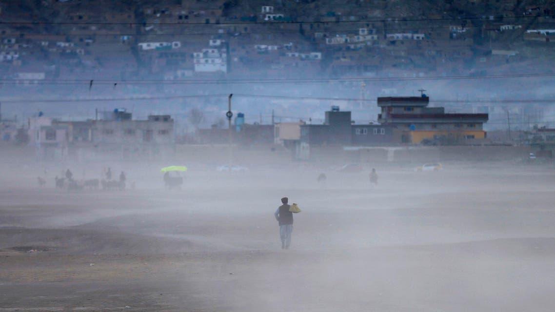An Afghan man heads home walking through a dust cloud as the sun sets in Kabul December 8, 2014. (Reuters)