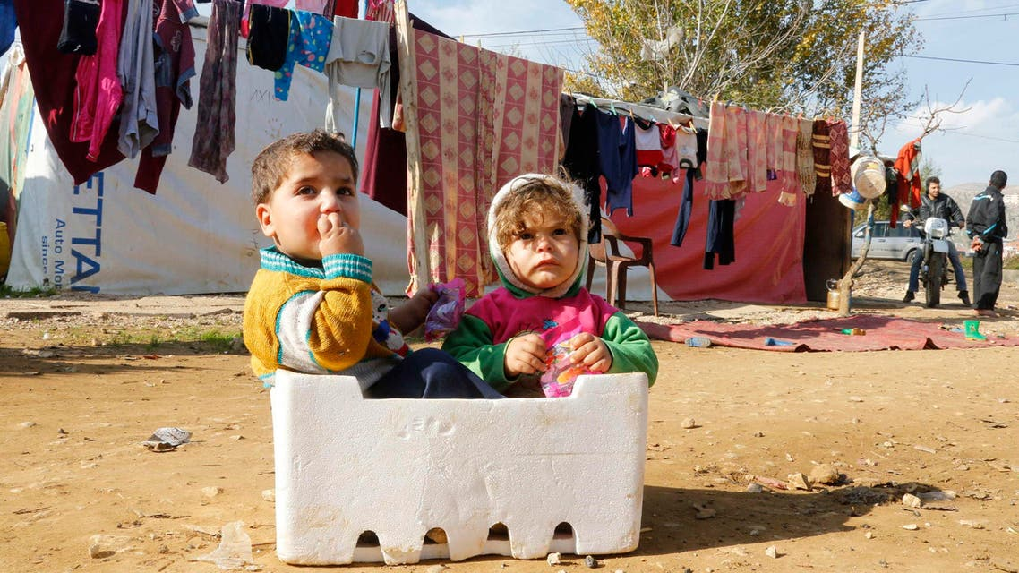 Syrian refugee children sit in a box at a makeshift settlement in Qab Elias in the Bekaa valley December 8, 2014. (Reuters)