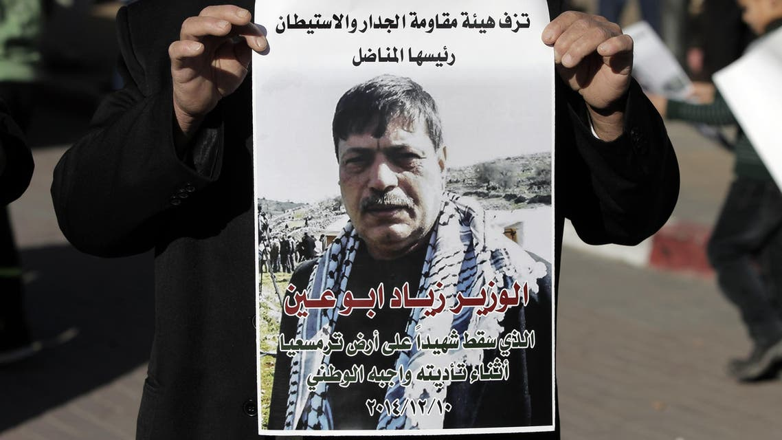 A Palestinian man carries a poster bearing the portrait of Palestinian Cabinet member Ziad Abu Ain, after the announcment of his death outside the main hospital in the West Bank city of Ramallah on December 10, 2014. AFP