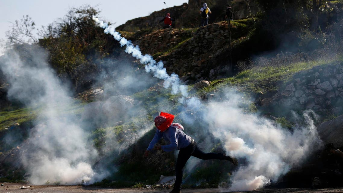 A Palestinian protester throws back a tear gas canister fired by Israeli troops during clashes near Israel's Ofer Prison, near the West Bank city of Ramallah December 13, 2014. (Reuters)