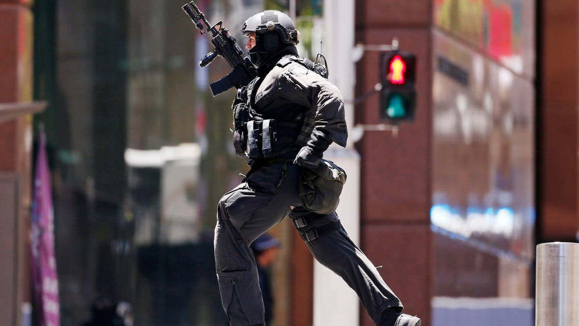 A police officer runs across Martin Place near Lindt cafe, where hostages are being held, in central Sydney December 15, 2014. (Reuters)