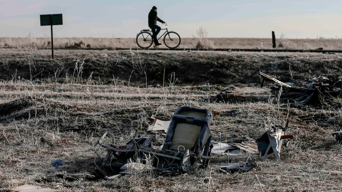 A man rides his bicycle past the wreckage of MH17, a Malaysia Airlines Boeing 777 plane, at the site of the plane crash near the village of Hrabove (Grabovo) in Donetsk region, December 15, 2014. (Reutres)