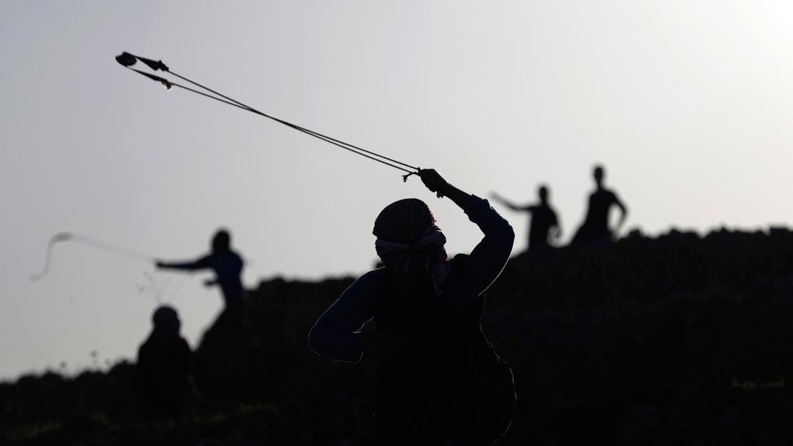 A Palestinian protester uses a slingshot to throw stones at Israeli troops during clashes near Israel's Ofer Prison, near the West Bank city of Ramallah December 13, 2014.  (Reuters)