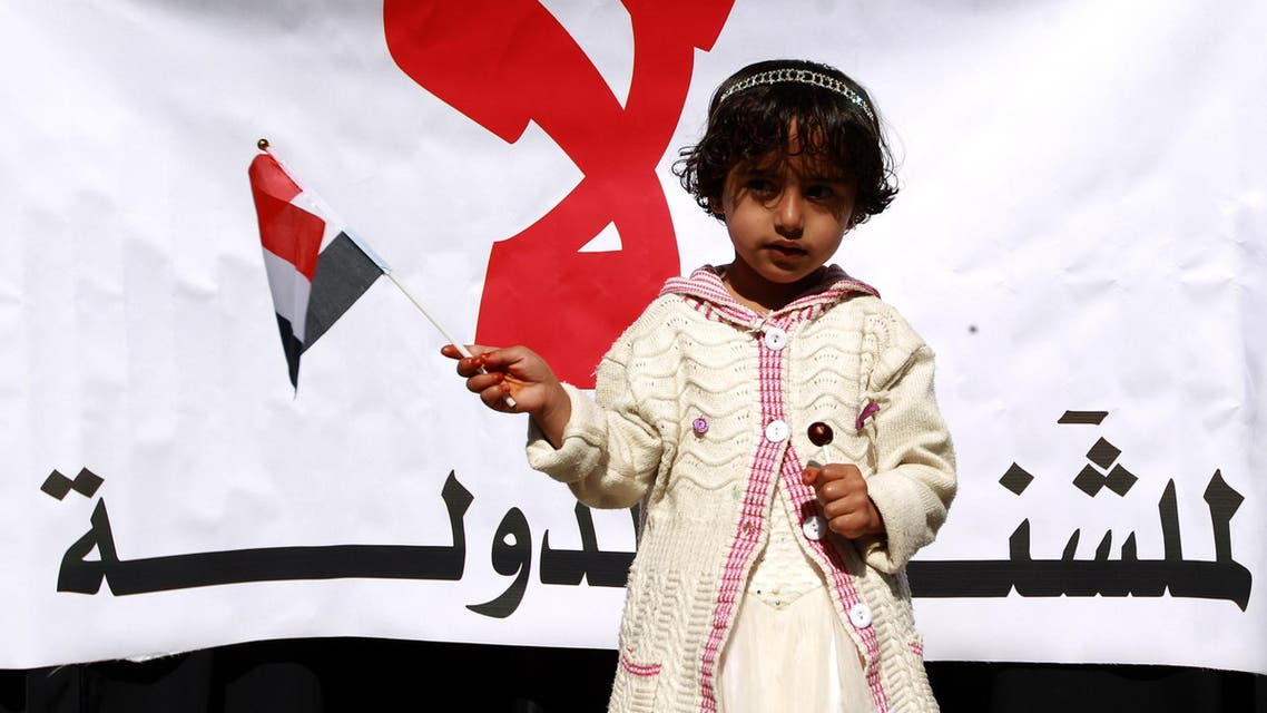 A Yemeni girl holds a national flag in front of a banner during a rally against the control of the country's main cities by Houthi rebels on December 13, 2014. (File photo: AFP)