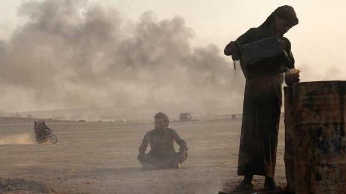 A man works at a makeshift oil refinery site in al-Mansoura village in Raqqa's countryside, in this file picture taken May 5, 2013. (Reuters) oil syria isis iran