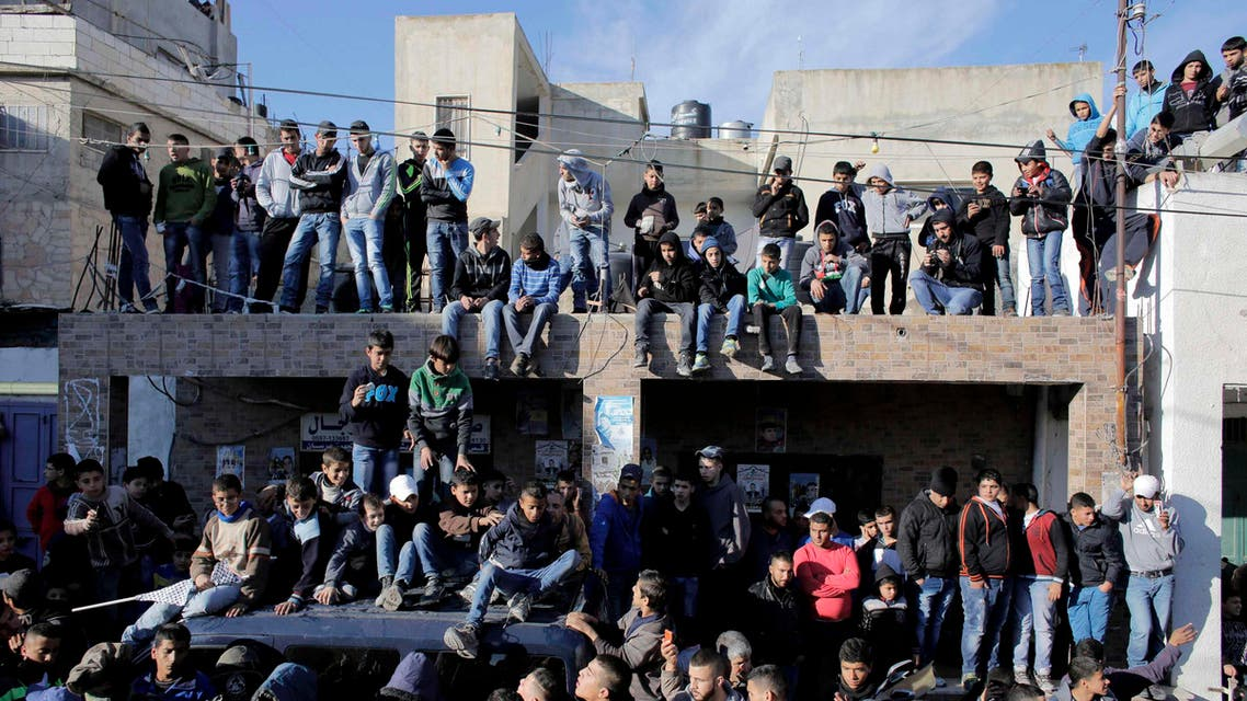 People watch the funeral of Palestinian Mahmoud Adwan in Qalandia refugee camp near the West Bank city of Ramallah December 16, 2014. (Reuters)