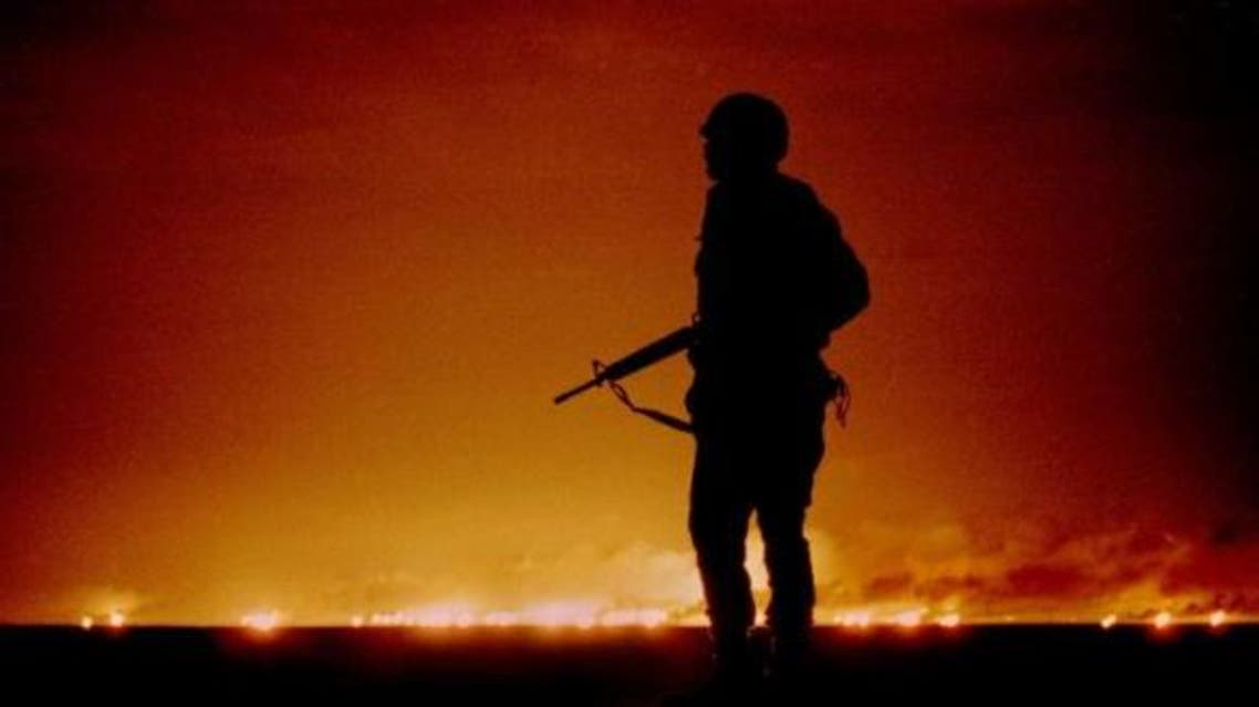A U.S. soldier stands night guard as oil wells burn in the distance in Kuwait, just south of the Iraqi border February 26, 1991.  (Reuters)