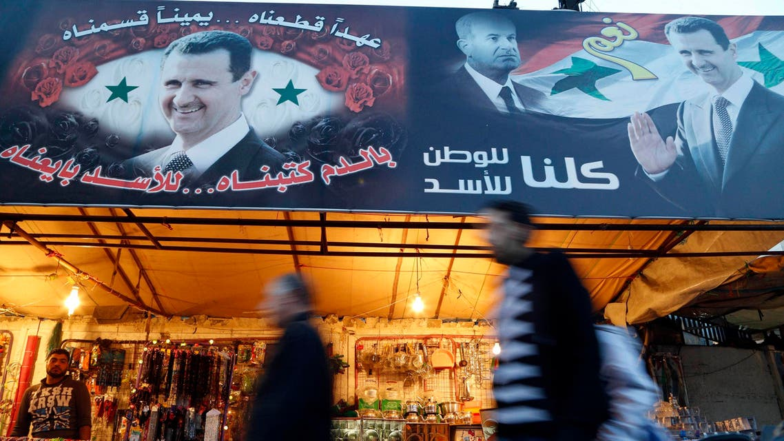 People walk past roadside stalls decorated with pictures of Syria's President Bashar al-Assad and his father, late president Hafez al-Assad (C), in the Baramkeh district of Damascus December 8, 2014. (Reuters)