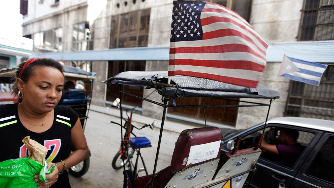 A woman walks past a bicycle taxi with the U.S. and Cuban flags in Havana December 17, 2014. (Reuters)