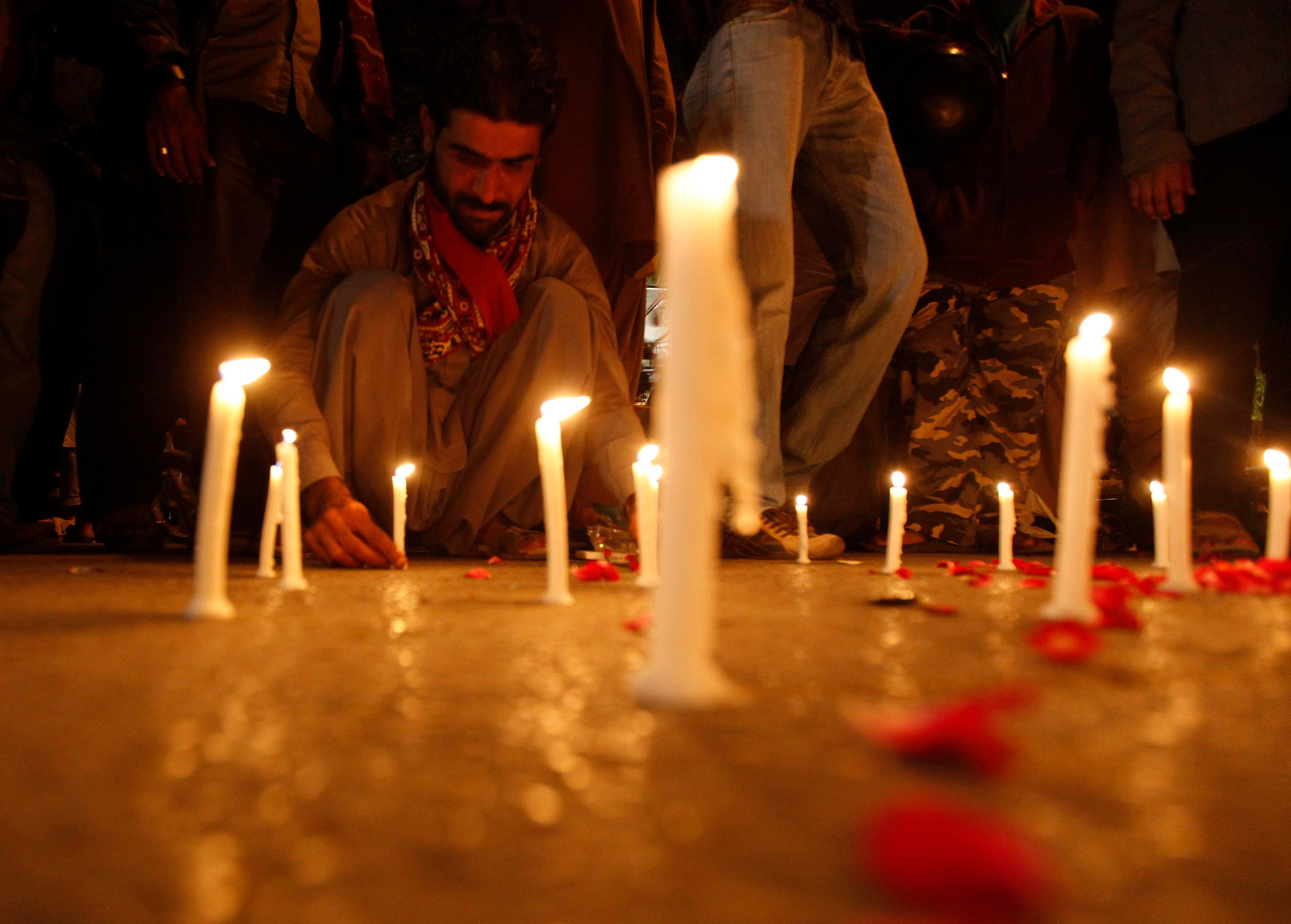 A man lights candles to mourn the victims from the Army Public School in Peshawar, which was attack by Taliban gunmen, in Karachi, December 16, 2014 reuters