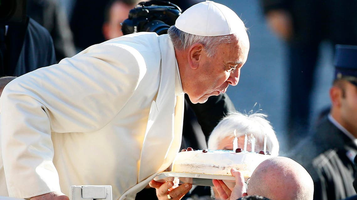 Pope Francis, who's 78th birthday is today, blows out candles on a cake as he arrives to lead his general audience at the Vatican, December 17, 2014. (Reuters)