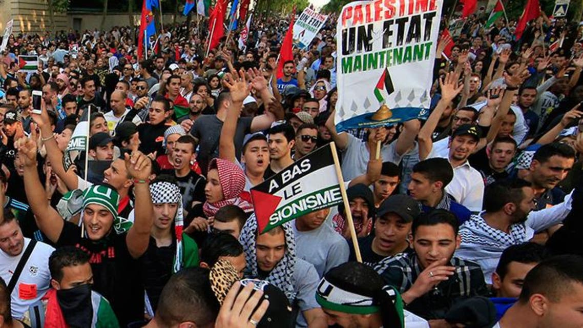 """ARCHIVE PHOTO: Pro-Palestinian protesters hold boards reading: """" Palestine, a state now"""" (R) and: """"down with zionism"""" during a demonstration, which had been authorized by police, against violence in the Gaza strip, in Paris July 23, 2014. Reuters"""