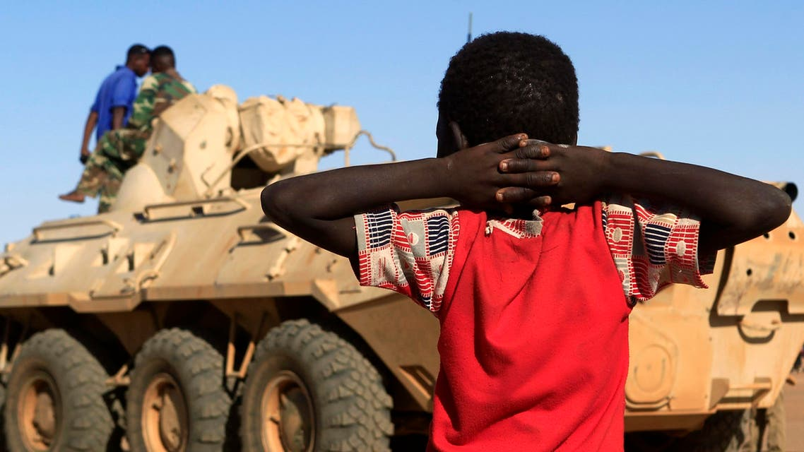A boy looks on as a military convoy of government forces accompanying Special Prosecutor for Crimes in Darfur Yasir Ahmed Mohamed and his team arrives in Tabit village in North Darfur November 20, 2014.
