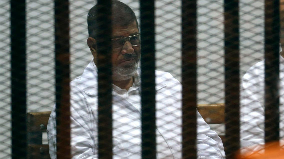 Former Egyptian President Mohamed Mursi sits behind bars with other Muslim Brotherhood members at a court in the outskirts of Cairo December 14, 2014. Egypt declared Mursi's Muslim Brotherhood a banned terrorist organization last December and Egyptian courts have sentenced hundreds of the group's members to death in mass trials that have drawn strong international criticism. Reuters