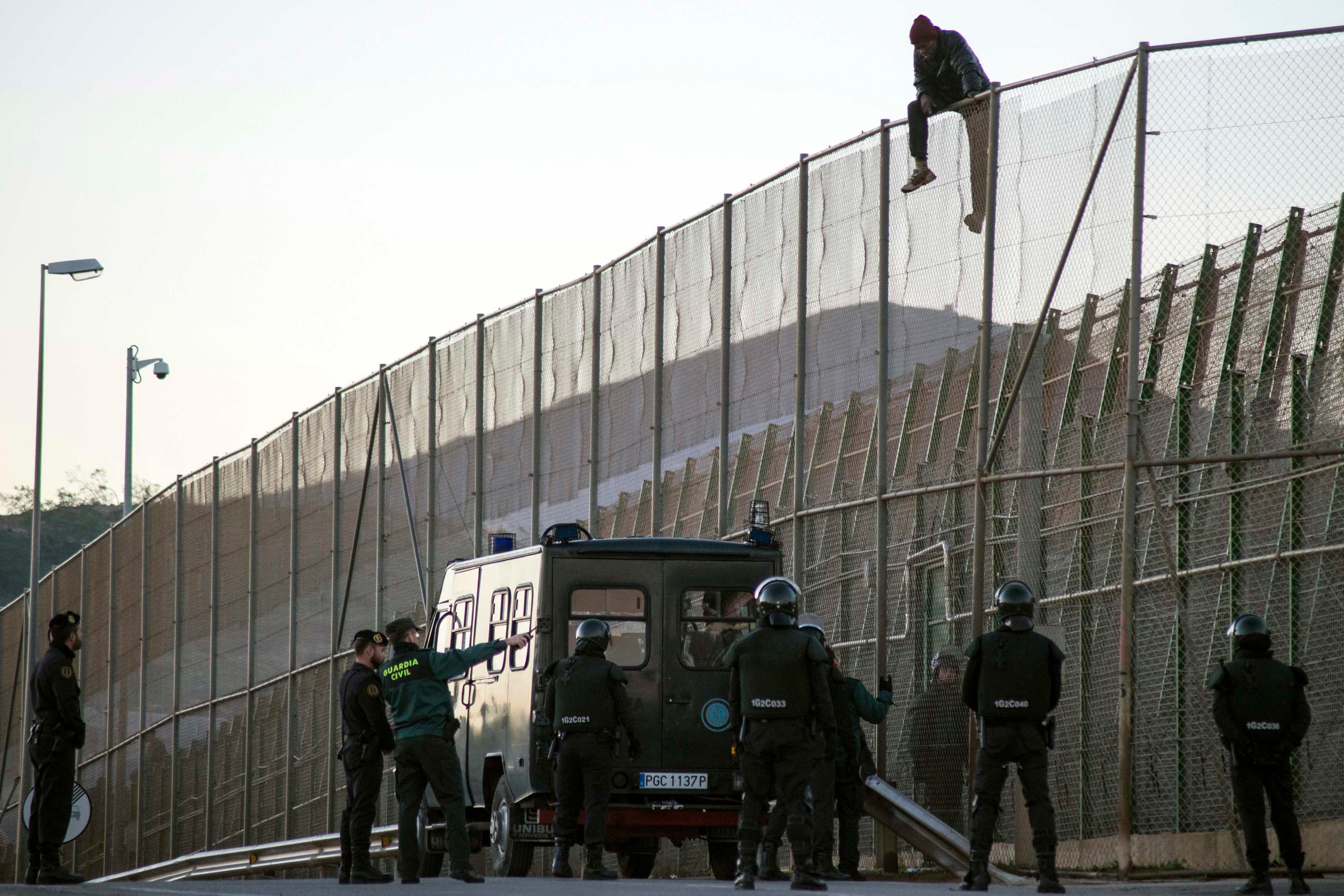 n African migrant sits atop a border fence, above Spanish Civil Guard officers, during an attempt to cross into Spanish territories, between Morocco and Spain's north African enclave of Melilla December 19, 2014. REUTERS