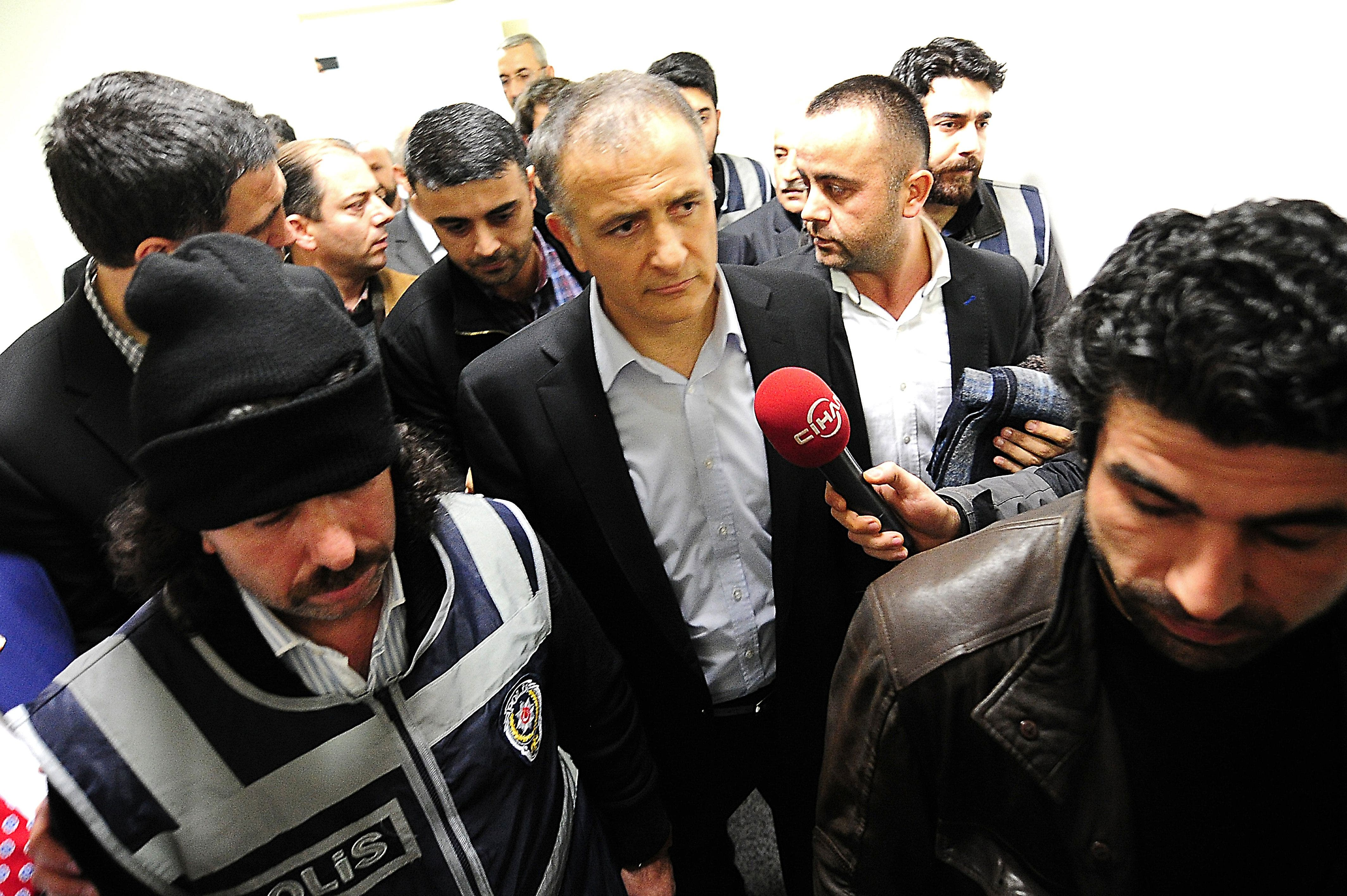 Turkey's Zaman newspaper editor-in-chief Ekrem Dumanli (C) is detained by counter-terror police at Zaman headquarters in Istanbul on December 14, 2014. AFP