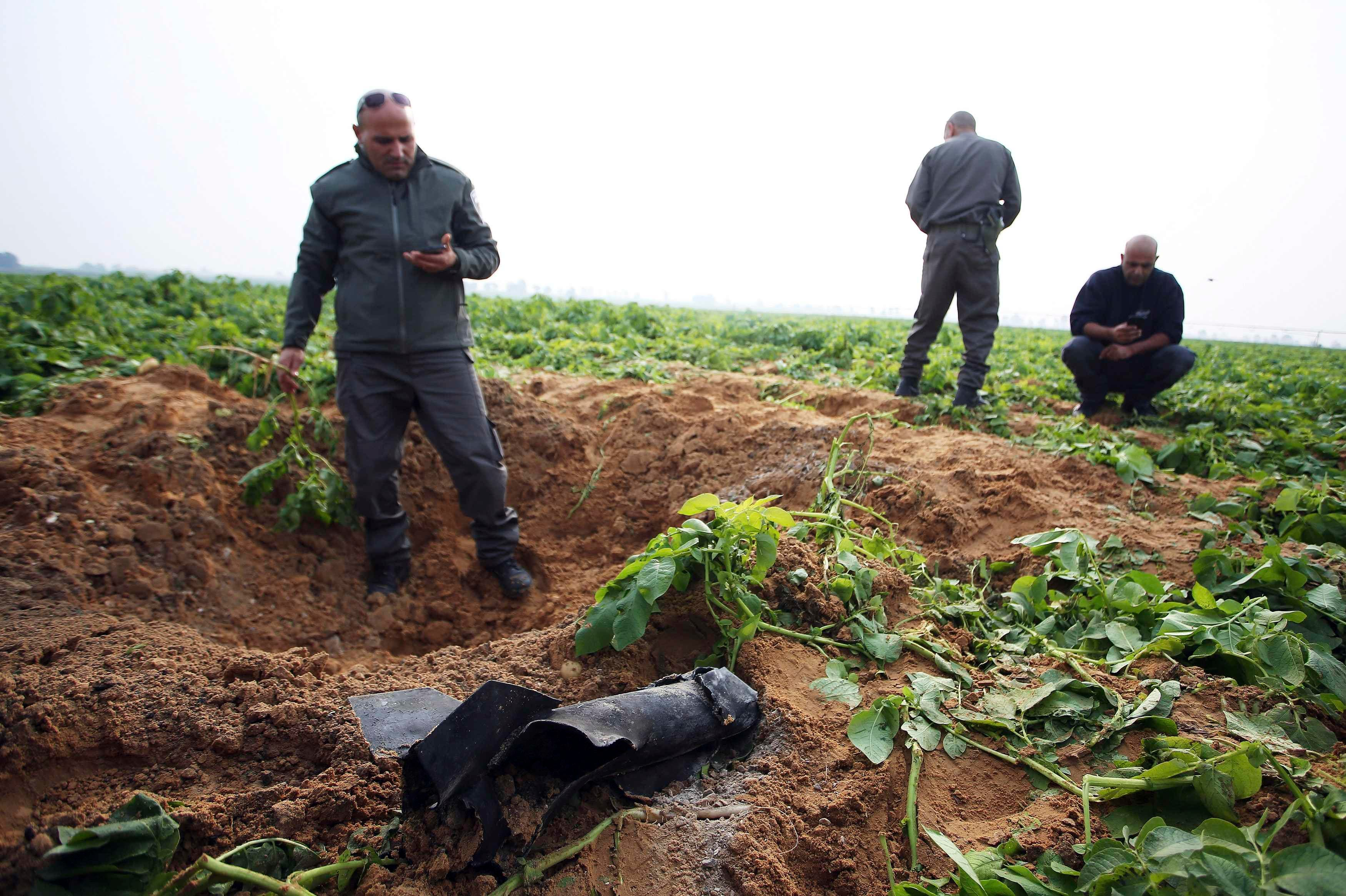 Israeli security forces stand next to the remains of a rocket that was fired from the Gaza Strip towards Israel on Friday, on the Israeli side of the border December 19, 2014. reuters
