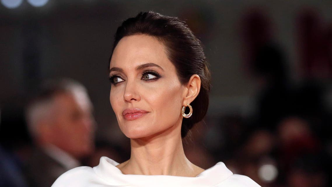 "Angelina Jolie poses for a photograph as she arrives for the UK premiere of ""Unbroken"" in central London November 25, 2014. REUTERS"