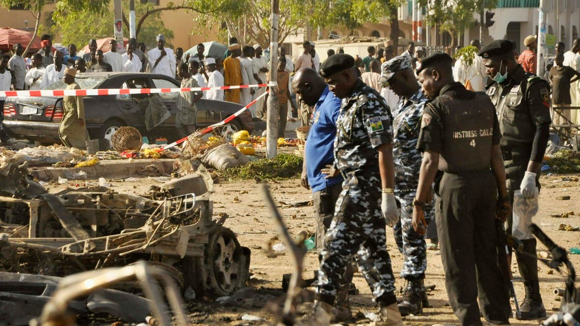 Bomb detection security personnel inspect the wreckage of a car believed to be used in the Kano Central Mosque bombing, November 28, 2014. (Reuters)
