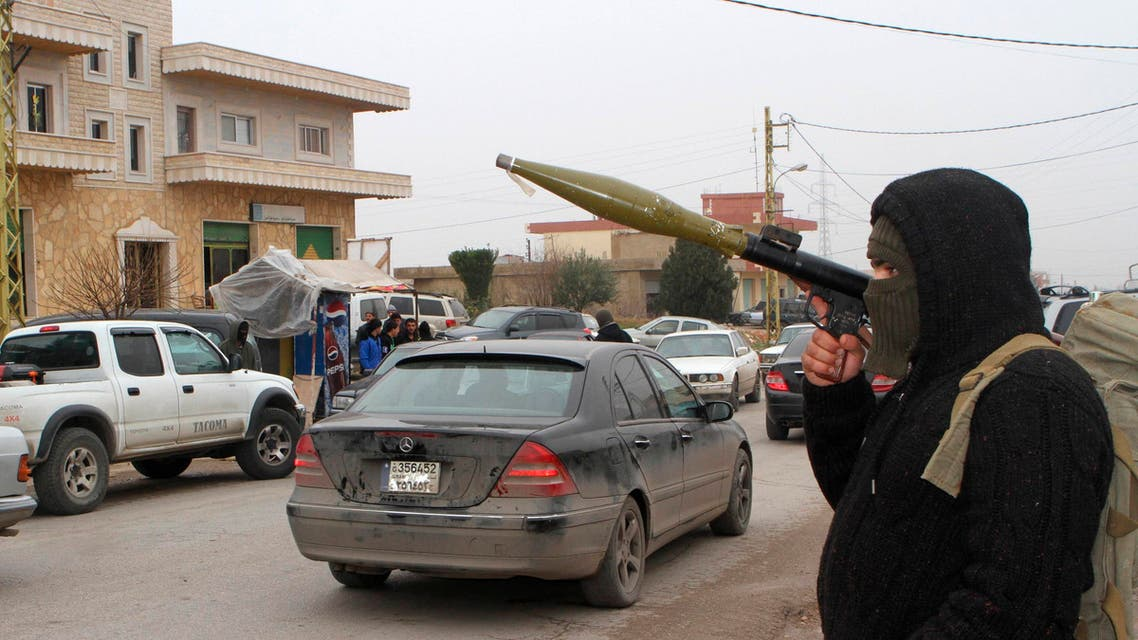 A masked man carries a rocket-propelled grenade (RPG) while manning a checkpoint in Bazalia village, home of Lebanese soldier Ali al-Bazzal who was killed by Nusra Front, on a road that links Arsal to Baalbek December 6, 2014. (Reuters)