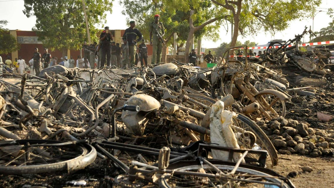 Police officers stand near wreckage at a scene of multiple bombings at Kano Central Mosque, Nigeria, Nov. 28, 2014. (Reuters)