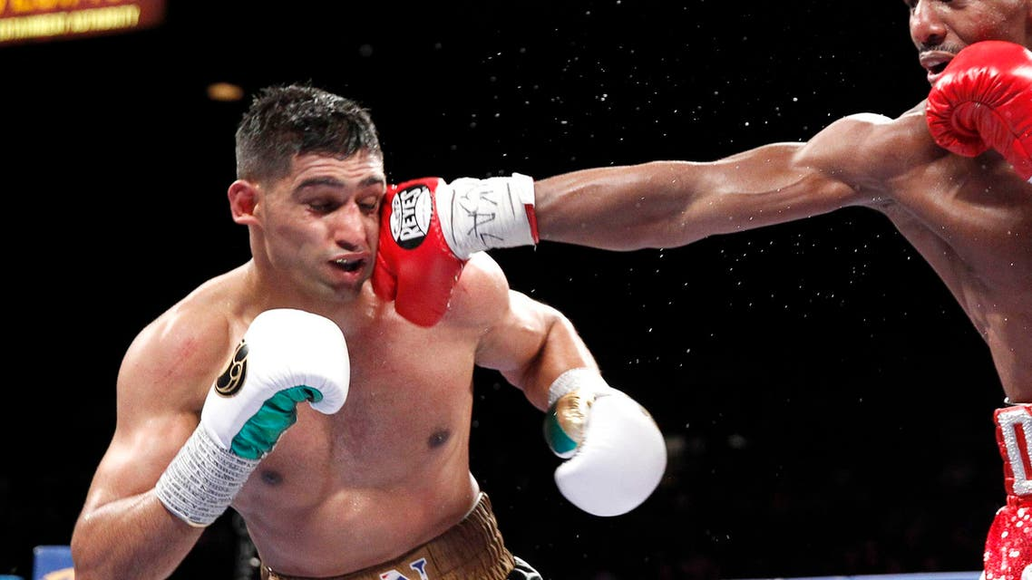 Welterweight boxer Amir Khan (L) of Britain takes a punch from Devon Alexander of the U.S. during a welterweight fight at the MGM Grand Garden Arena in Las Vegas, Nevada December 13, 2014. (Reuters)