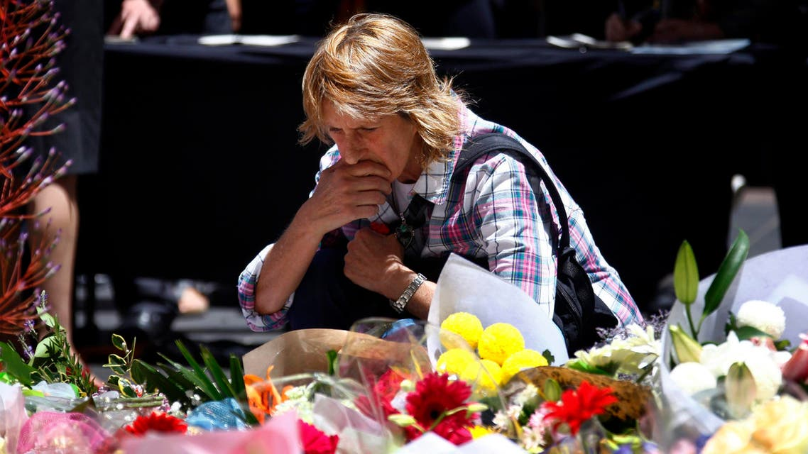A woman reacts after placing a floral tribute amongst thousands of others that have been placed near the cafe where hostages were held for over 16-hours, in central Sydney December 16, 2014. reuters
