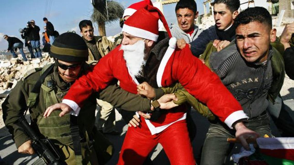 Palestinian protesters wearing Santa Claus costumes scuffle with Israeli soldiers during clashes at Bethlehem checkpoint, West Bank. (Photo courtesy: Palestinian News Network)