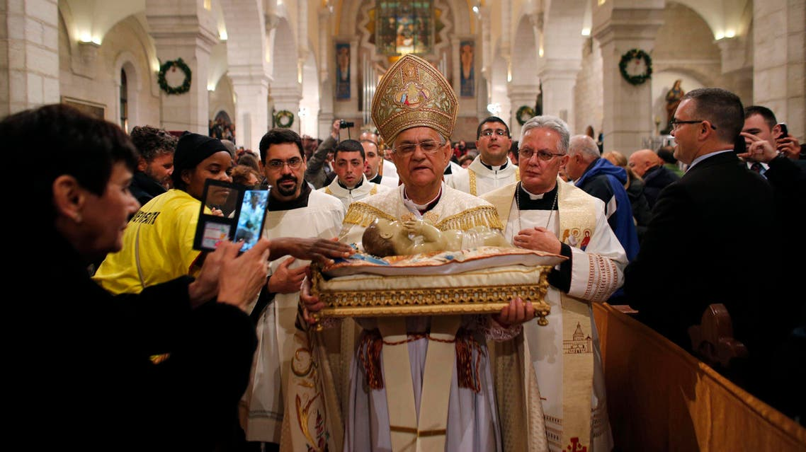 The Latin Patriarch of Jerusalem Fouad Twal carries a statuette of baby Jesus during a Christmas Midnight Mass at the Church of the Nativity in the West Bank town of Bethlehem December 25, 2014. reuters