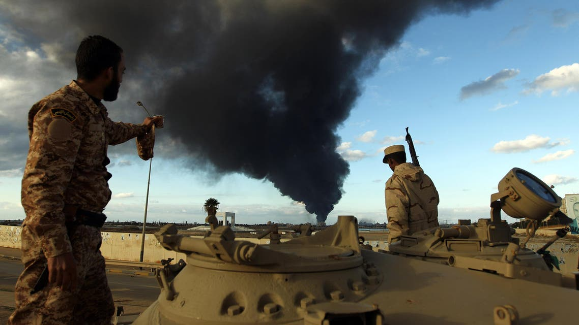 Members of the Libyan army stand on a tank as heavy black smoke rises from the Benghazi's port in the background on Dec. 23, 2014. (AFP)