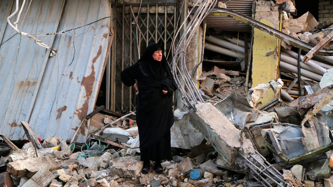 A woman looks at damages at the site of a car bomb attack in Baghdad's Sadr City , December 5, 2014. Reuters