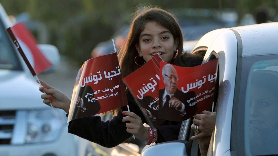 A young girl holds flags from a car as supporters of Tunisian newly-elected President Beji Caid Essebsi celebrate his victory on December 22, 2014 in Tunis. AFP