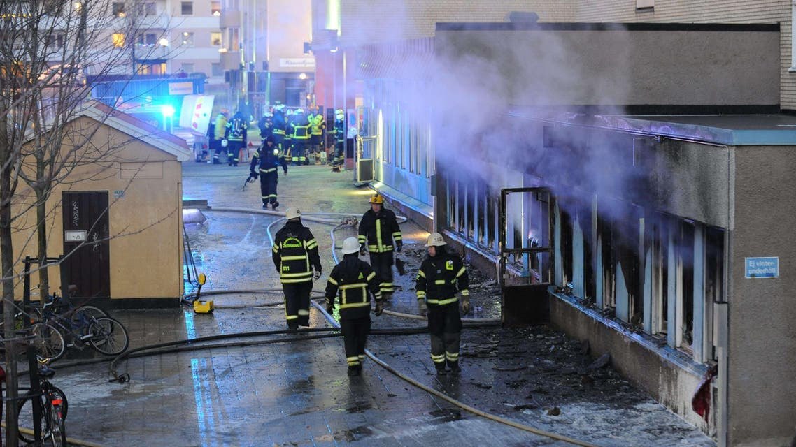 Smoke rises from the interior of a destroyed cellar mosque as firefighters walk in front of the building after an arson attack on December 25, 2014 in Eskilstuna, central Sweden. AFP