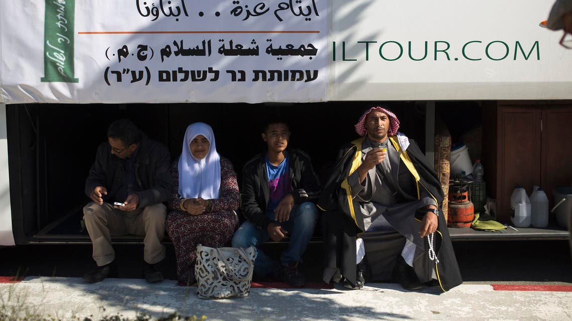 Activists sit in the trunk of a bus as they wait for a group of Palestinian children at the Erez border crossing between Israel and northern Gaza Strip December 28, 2014.  (Reuters)