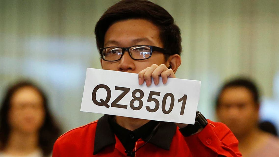 A Changi Airport staff holds up a sign to direct possible next-of-kins of passengers of AirAsia flight QZ 8501 from Indonesian city of Surabaya to Singapore, at Changi Airport in Singapore December 28, 2014