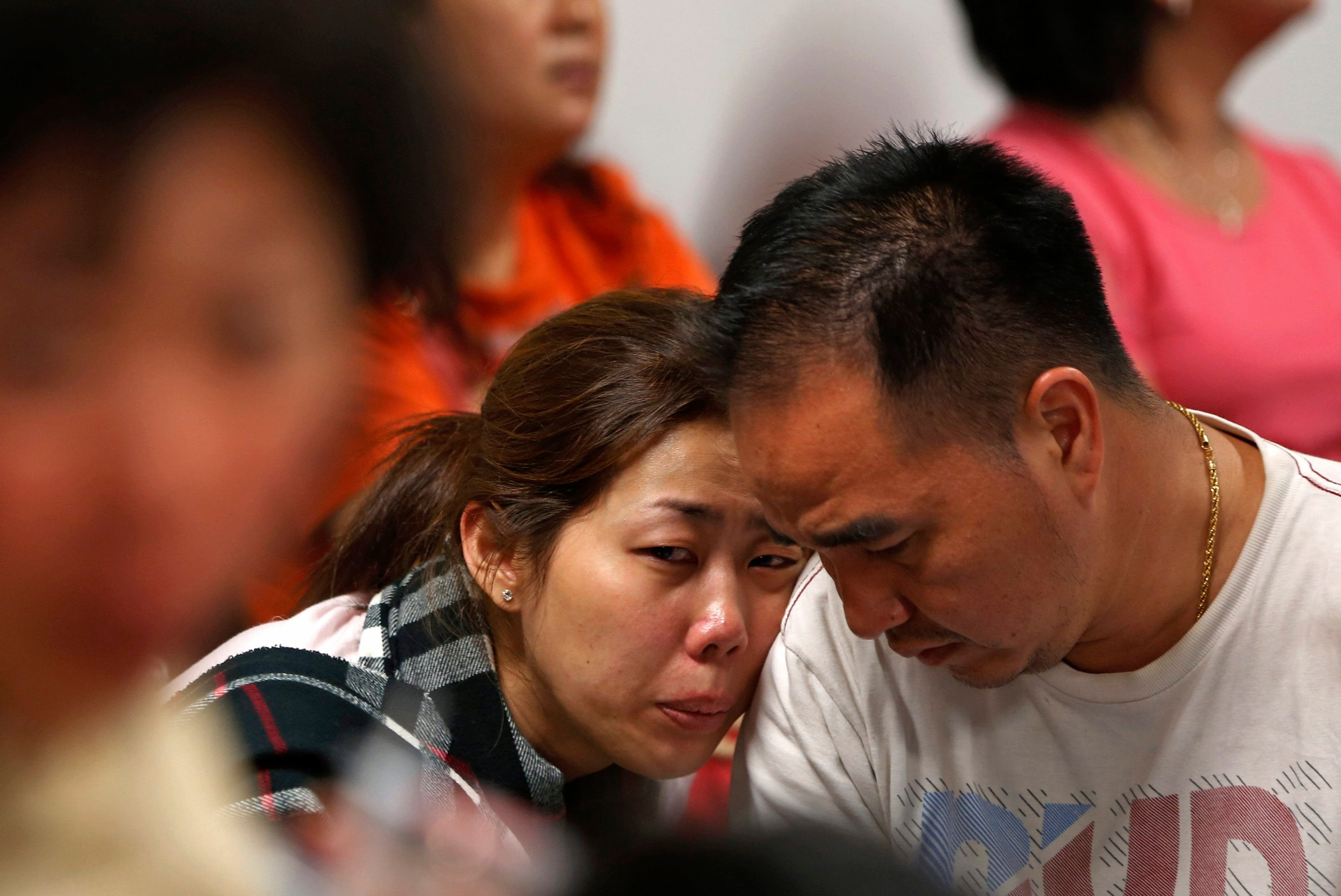 Family of passengers onboard AirAsia flight QZ8501 react at a waiting area in Juanda International Airport, Surabaya December 28, 2014. (Reuters)