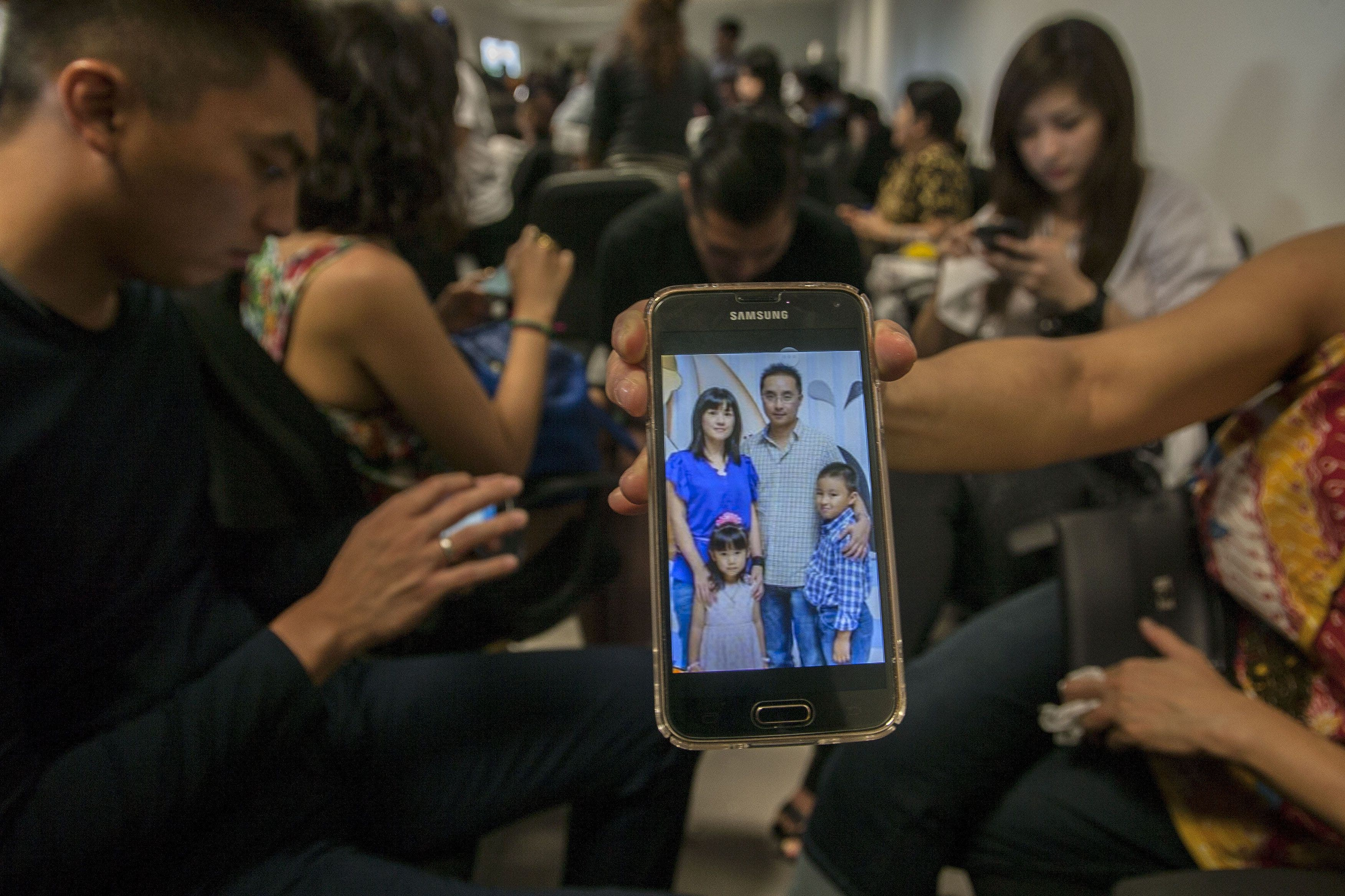 A relative shows a picture of alleged passengers who were travelling on missing Malaysian air carrier AirAsia flight QZ8501. (AFP)