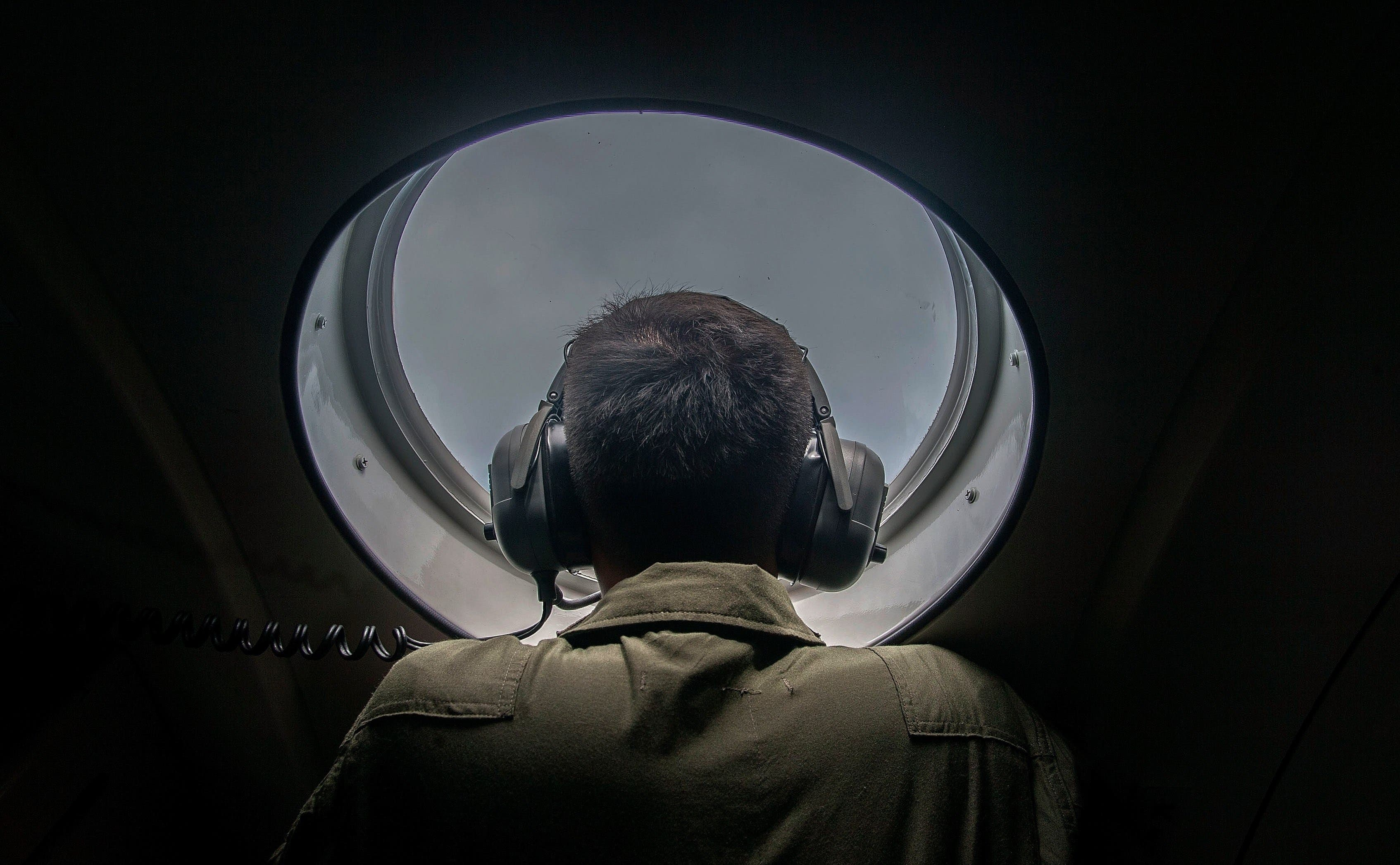 A member of the Indonesian military looks out of the window during a search and rescue (SAR) operation for missing Malaysian air carrier AirAsia flight QZ8501, over the waters of the Java Sea on Dec. 29, 2014.  (AFP)
