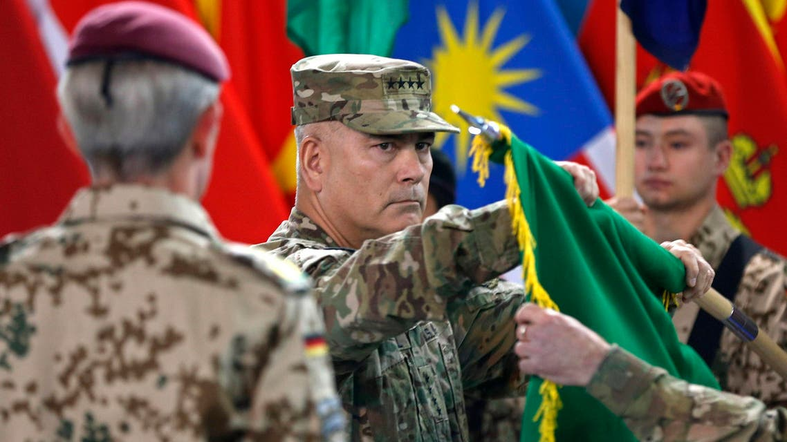 U.S. General John Campbell (C), commander of NATO-led International Security Assistance Force (ISAF), folds the flag of the ISAF during the change of mission ceremony in Kabul, December 28, 2014.