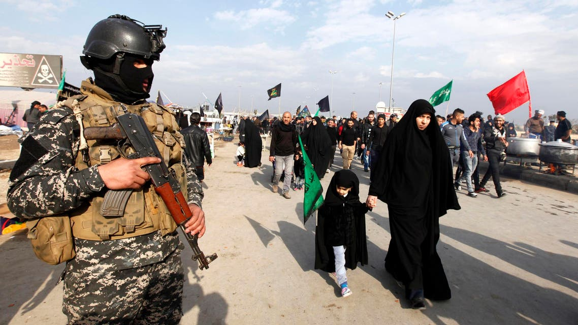 A police officer stands guard as Shi'ite pilgrims make their way to the holy city of Kerbala, ahead of the holy Shiite ritual of Arbaeen, in Baghdad, December 10, 2014. (File photo: Reuters)
