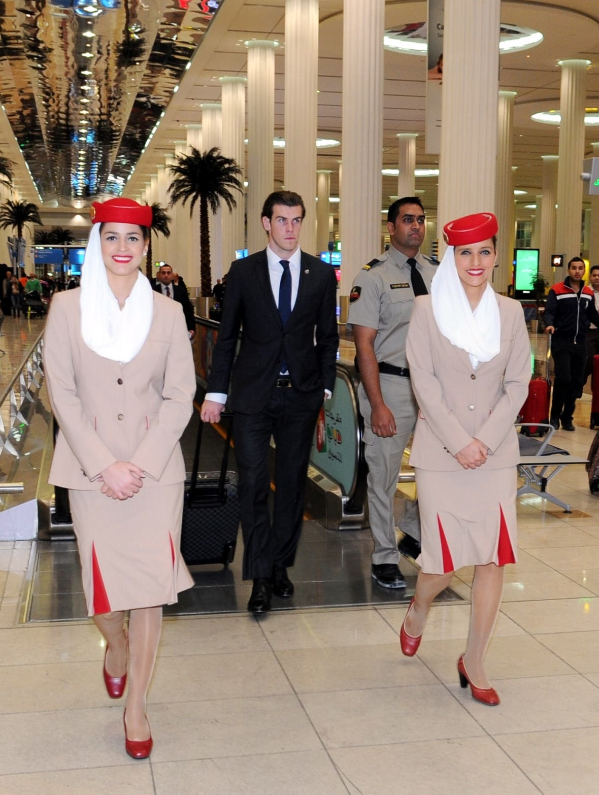 1 Emirates cabin crew escort Gareth Bale through the terminal at Dubai International Airport. (Emirates)