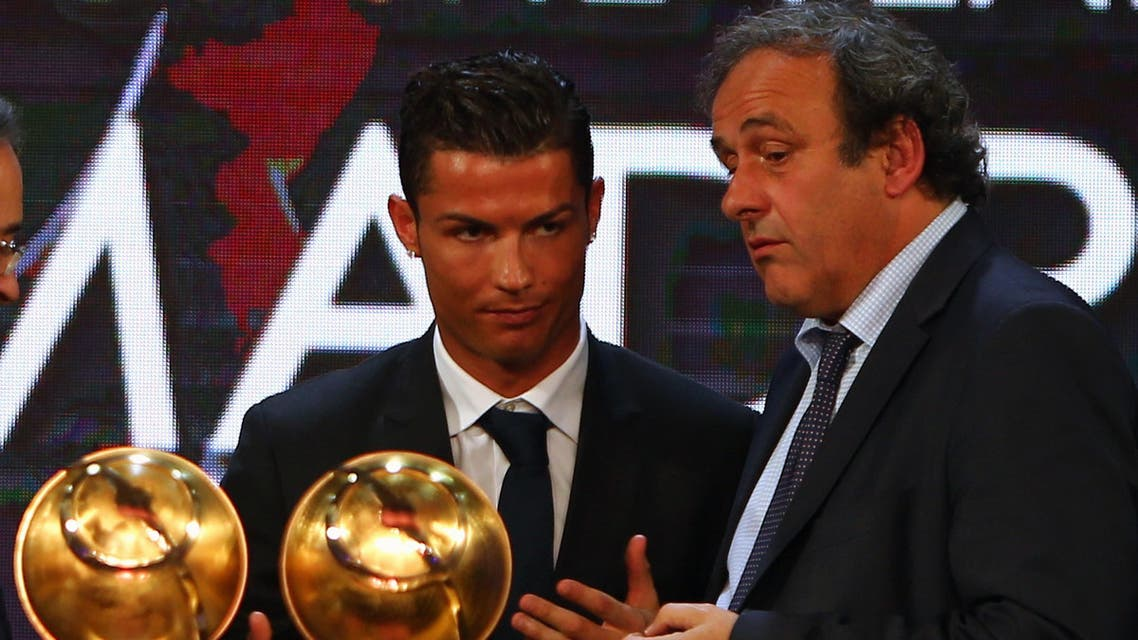 """Real Madrid's Portuguese football player Christiano Ronaldo (L) talks with UEFA President Michel Platini after hereceives the """"Best Player of the Year"""" award during the Globe Soccer Awards Ceremony at the end of the 9th International Sports Conference on December 29, 2014 in Dubai. AFP"""