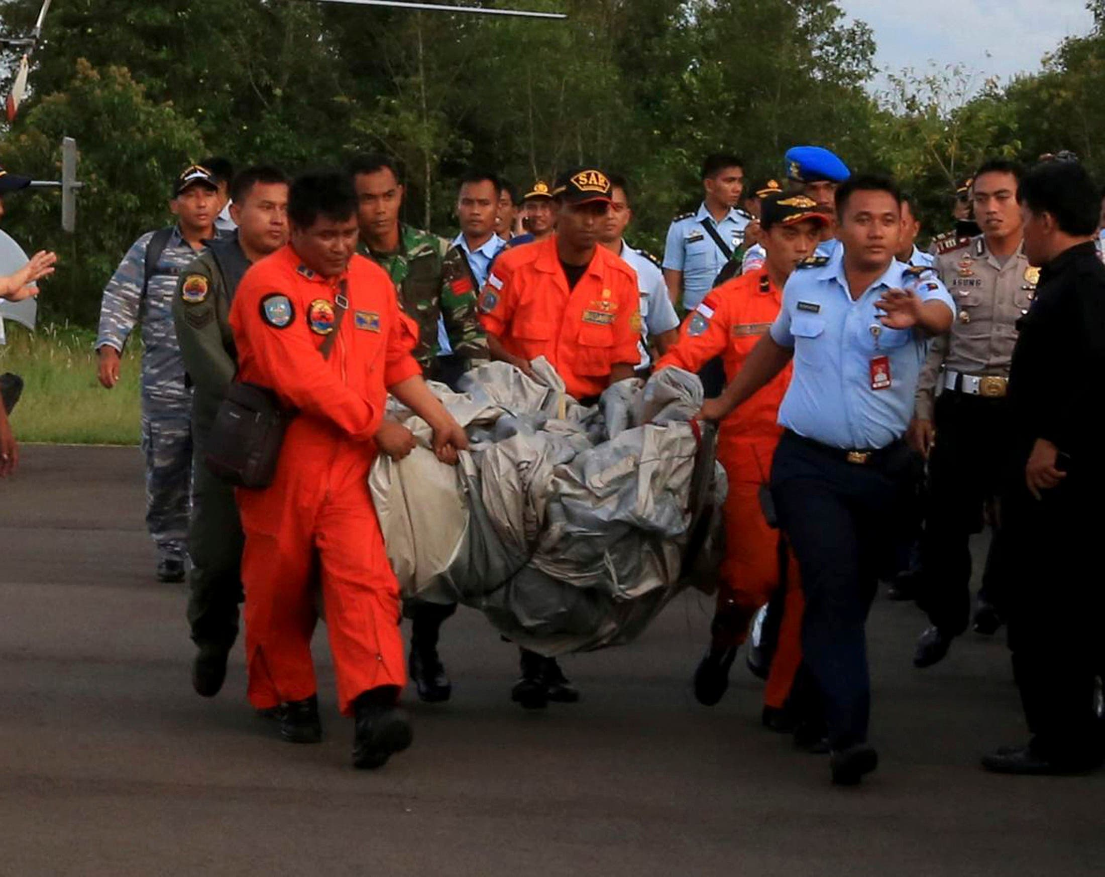Members of the Search and Rescue Agency carry debris recovered from the sea presumed from missing Indonesia AirAsia flight QZ 8501. (Reuters)