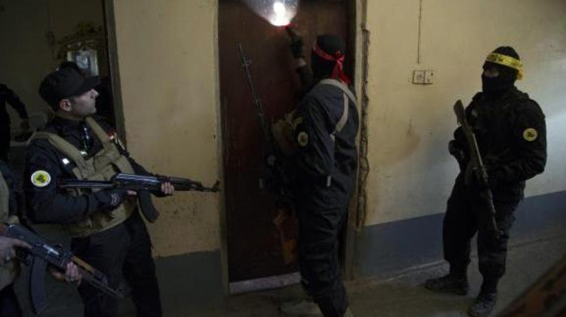 Fighters from the Shi'ite Kata'ib Imam Ali (Imam Ali Brigades) militia search a house after taking control of a village from Islamist State militants, on the outskirts of Dhuluiya, north of Baghdad December 29, 2014. (Reuters)