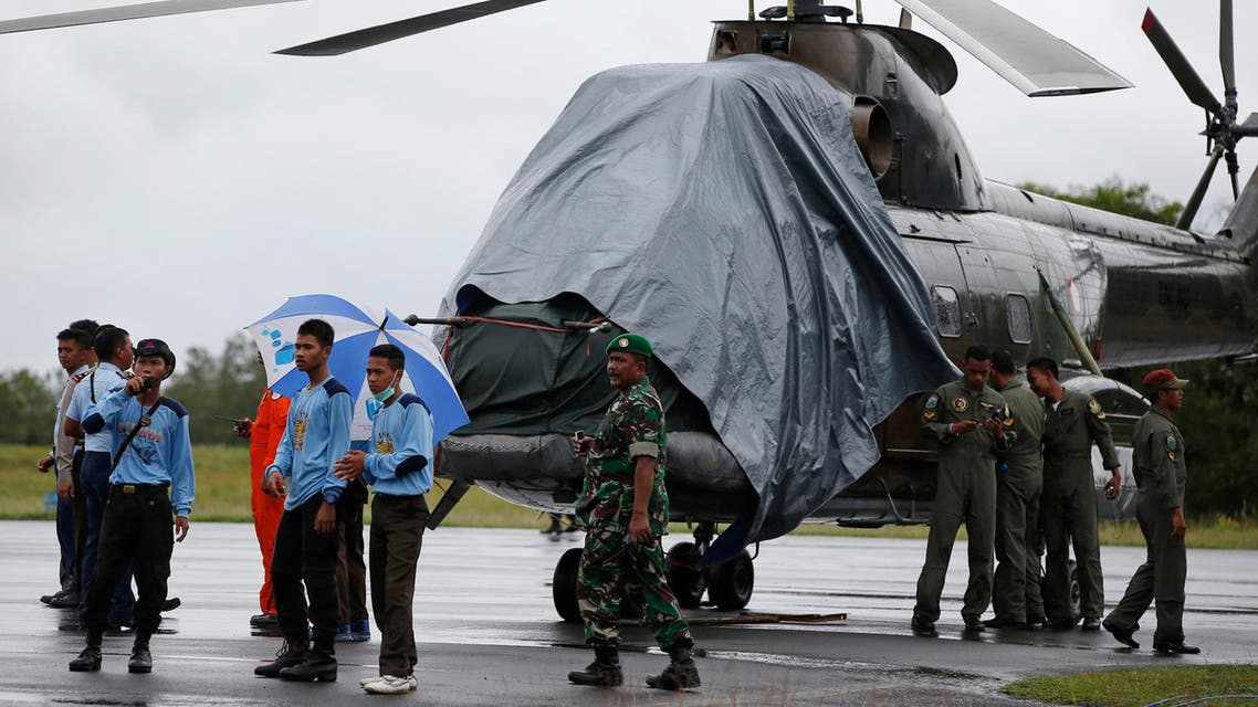 An Indonesian military helicopter, used in recovery efforts for the missing AirAsia plane, sits idle on the tarmac at Iskandar Airport during bad weather in Pangkalan Bun, Central Kalimantan, Dec. 31, 2014. (Reuters)