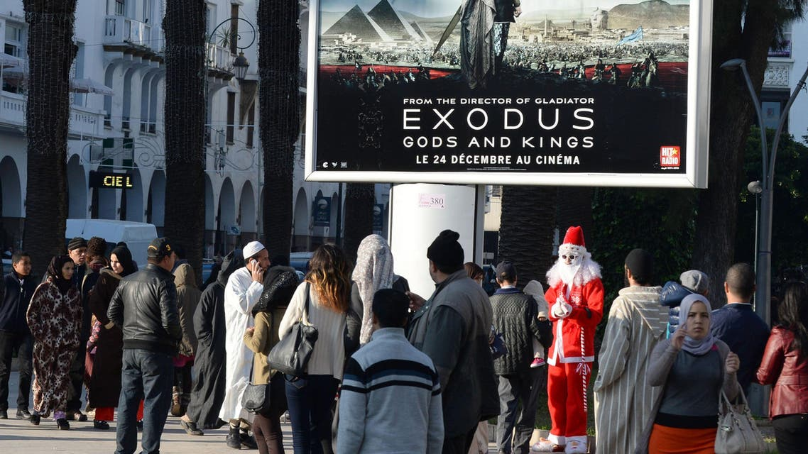 """People walk past a billboard for the Hollywood biblical epic movie """"Exodus: Gods and Kings"""" displayed in the Moroccan capital Rabat on December 26, 2014. AFP"""